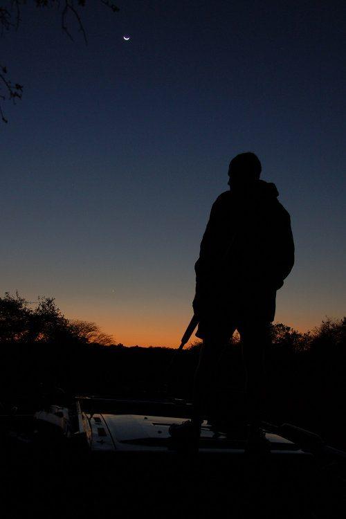 Game ranger silhouette at dusk