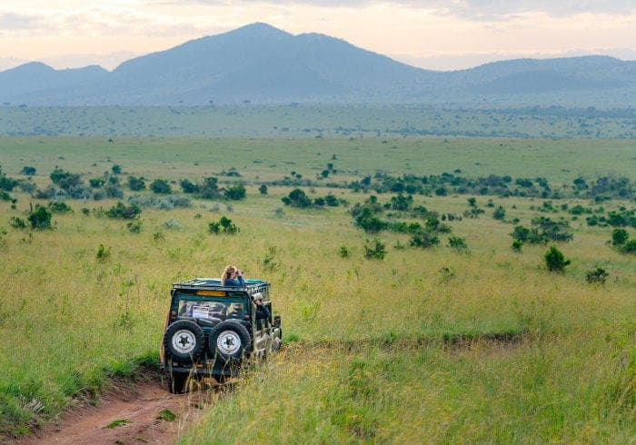 Safari jeep driving through typical African landscape
