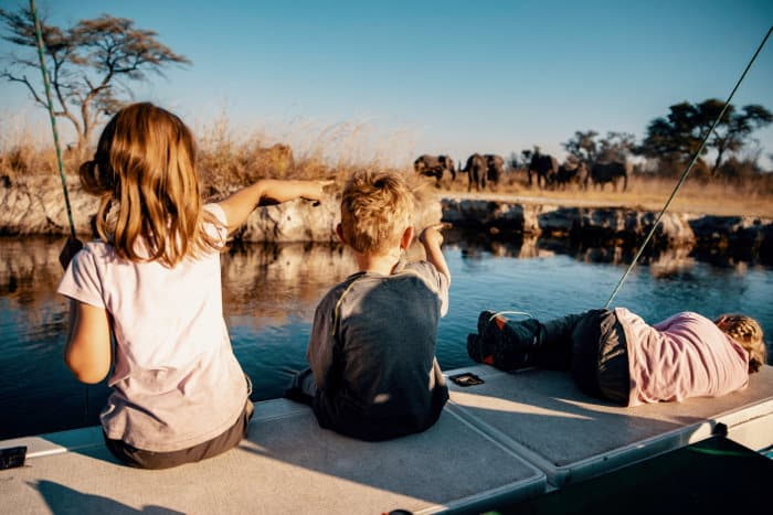Children observing elephants from a boat in Kwando