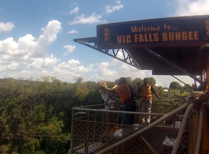 Raising arms at shoulder length before bungee jumping off Victoria Falls Bridge