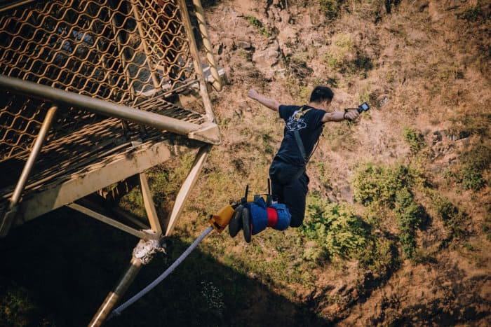 Man jumps off the Victoria Falls bungee jump platform with a GoPro in his hand