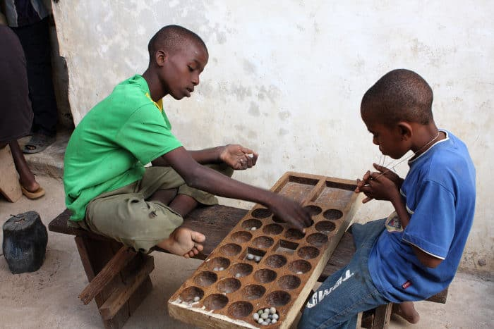 Children playing a traditional board game - Bao - in Lamu