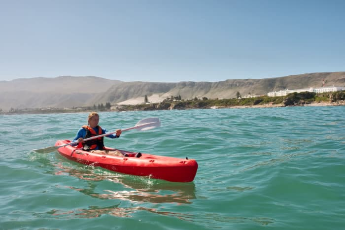 Young man paddles in sea kayak, during the whale watching season in Hermanus
