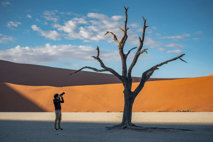 Young man taking a picture of a dead tree in Deadvlei area, Namibia