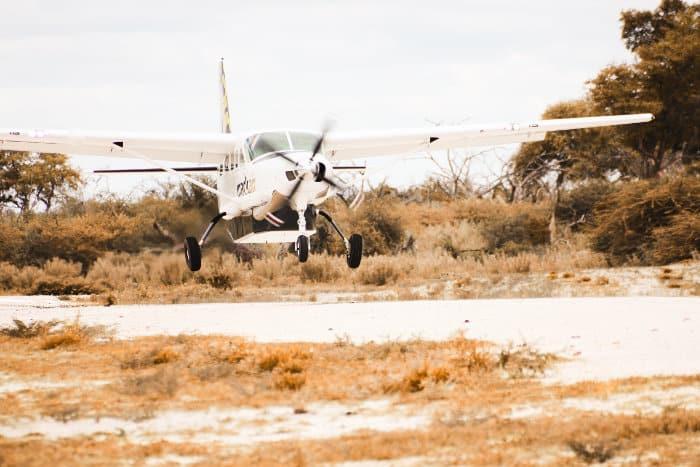A light aircraft lands on a bush strip in the Okavango