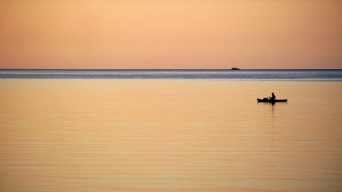 Boat silhouette against an orange sunset on Lake Malawi