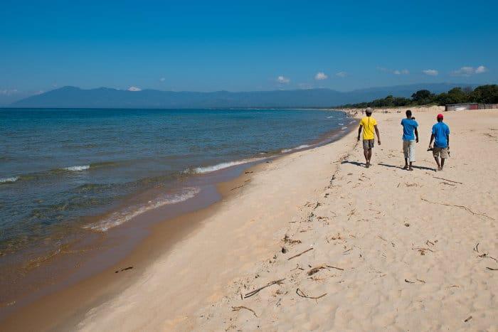 Three locals walking along the lakeshore in Kande Beach, Lake Malawi