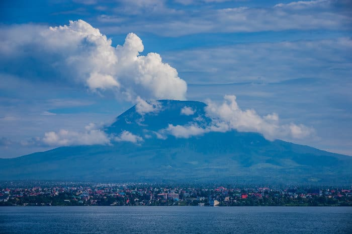 Clouds of smoke emanate from Mount Nyiragongo, with the city of Goma lying beneath