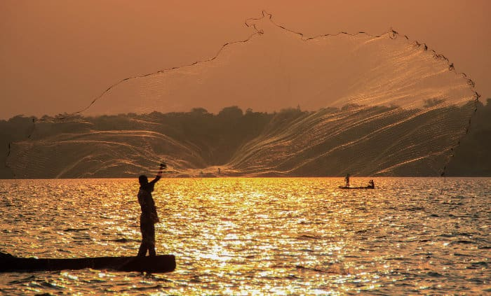 Local fisherman throwing his net at sunset, Lake Victoria