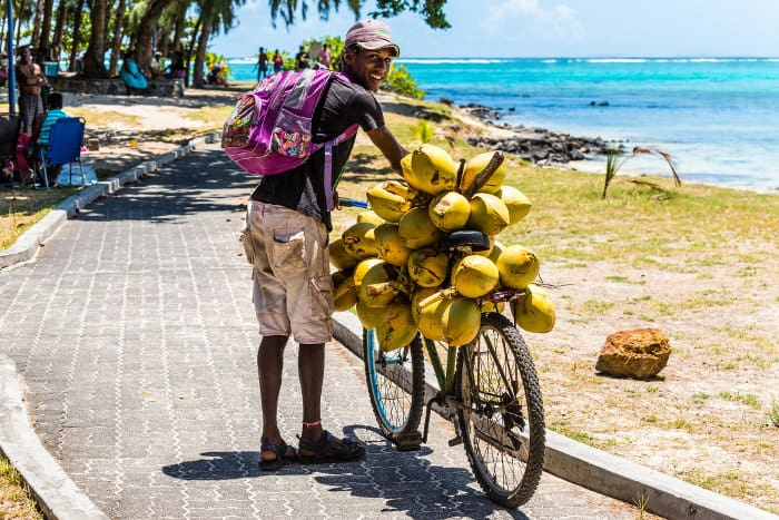 Young man selling coconuts from his bicycle, Blue Bay, Mauritius