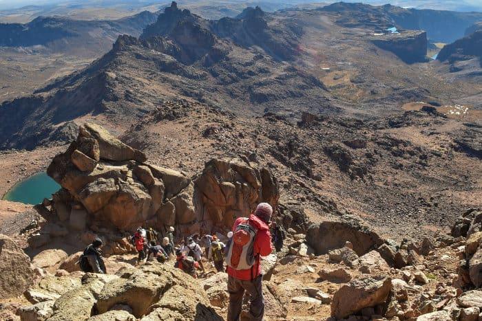 Hikers progressing on Mount Kenya's volcanic landscape