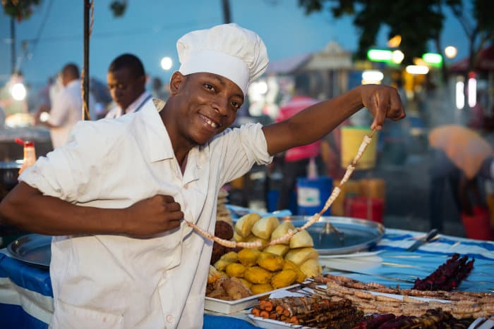 A friendly chef proudly shows off the food he is selling, in Forodhani Gardens, Zanzibar