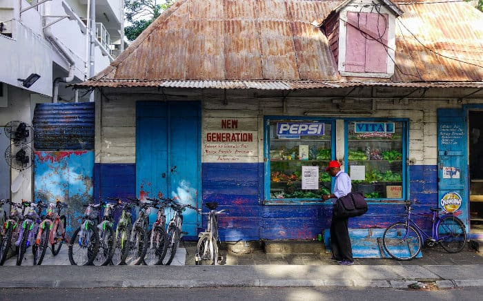 Man standing outside a local grocery store in Port Louis, Mauritius