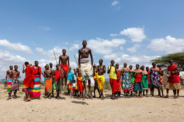 A group of Samburu people, wearing brightly coloured traditional attire, perform a local dance