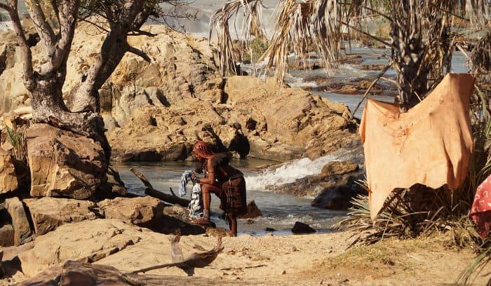 Himba woman cleaning clothes at Epupa Falls, Namibia