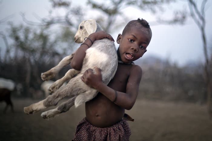 Cute Himba boy posing with a baby goat in his arms