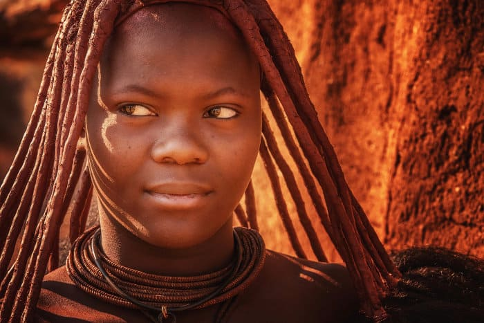 Young himba woman, wearing the traditional hairstyle, leather necklaces and red ochre paste on her skin