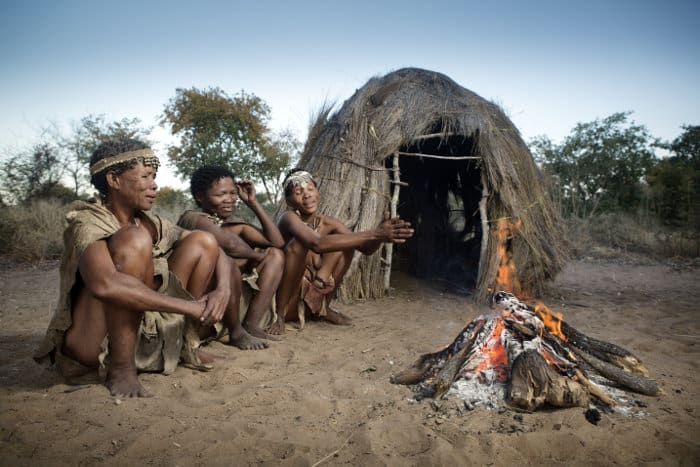 San bushmen chatting around a fire at dusk, Namibia