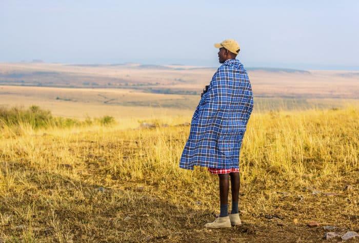 Safari guide with blue Shuka, scanning the area for wildlife across the Masai Mara plains