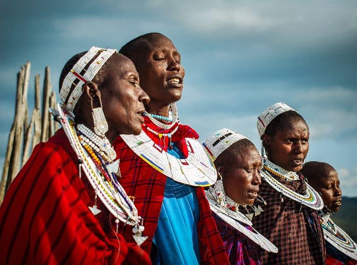 Maasai women singing, wearing colourful traditional jewellery