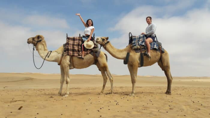 Two tourists riding camels in the Namib desert
