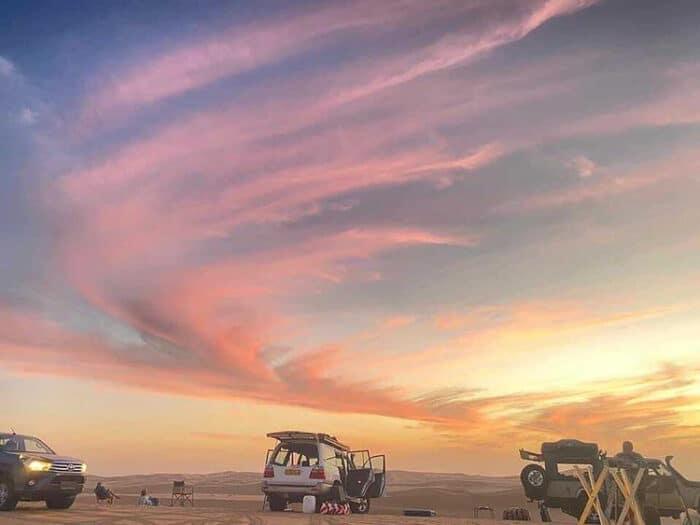 Three four wheel drives at sunset, Namib desert