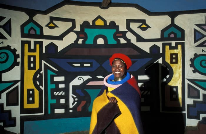 Ndebele woman in traditional clothing, against typical wall painting