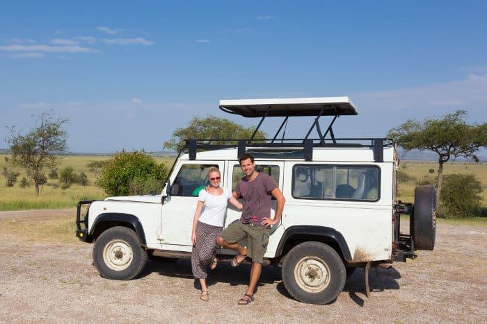 Couple on safari in Tanzania, posing in front of their four wheel drive